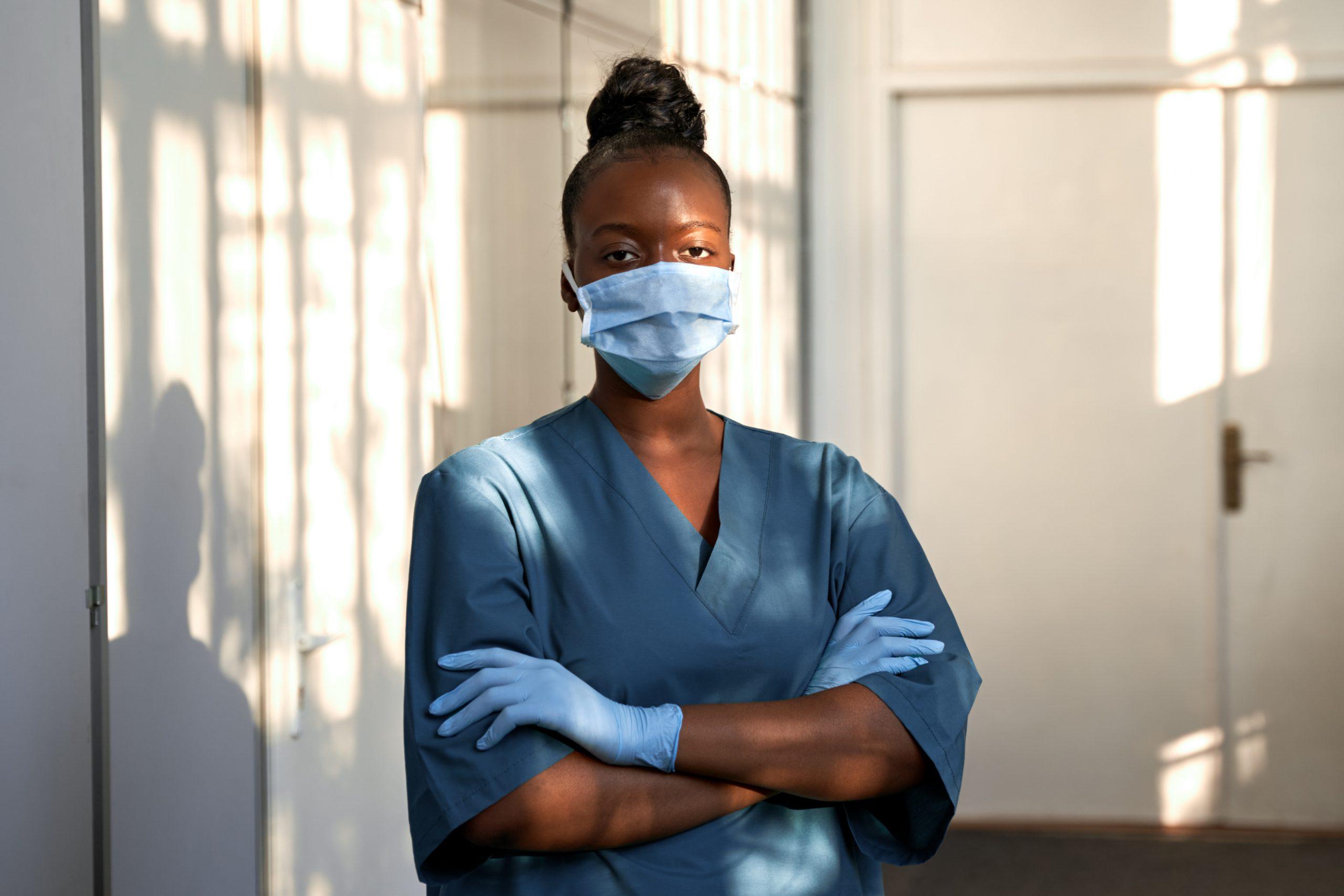 Confident african nurse wear blue uniform, face mask, standing in hospital.