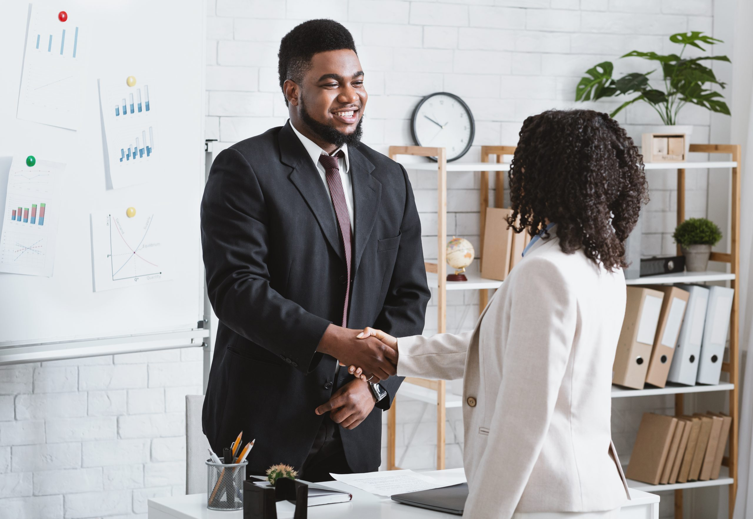 Joyful HR manager shaking hands with millennial applicant at job interview at company office