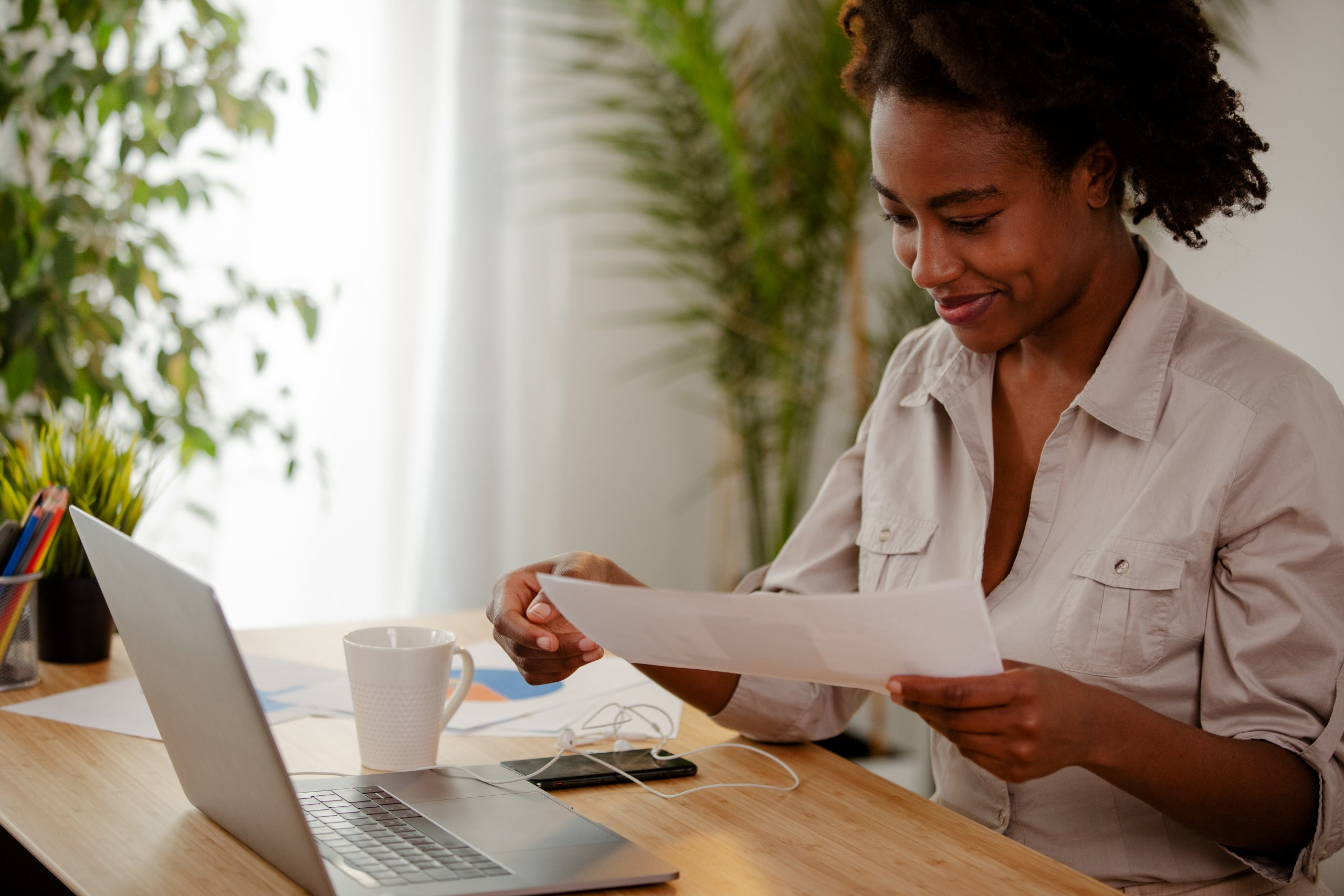 Smiling Afro American businesswoman working from home, drinking a coffee and holding some papers.